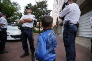 Un enfant rom encadré par des policiers, le 27 août 2012 à Evry. (Kenzo Tribouillard. AFP)